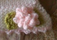 {crocheted flower and leaves hand-stitched onto brim}